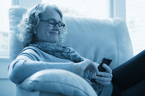 Woman relaxing on a chair and looking at her phone screen