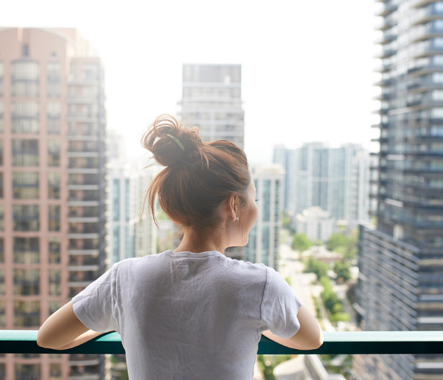 woman looking at city over terrace from apartment