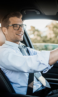 Professional man with glasses driving a car